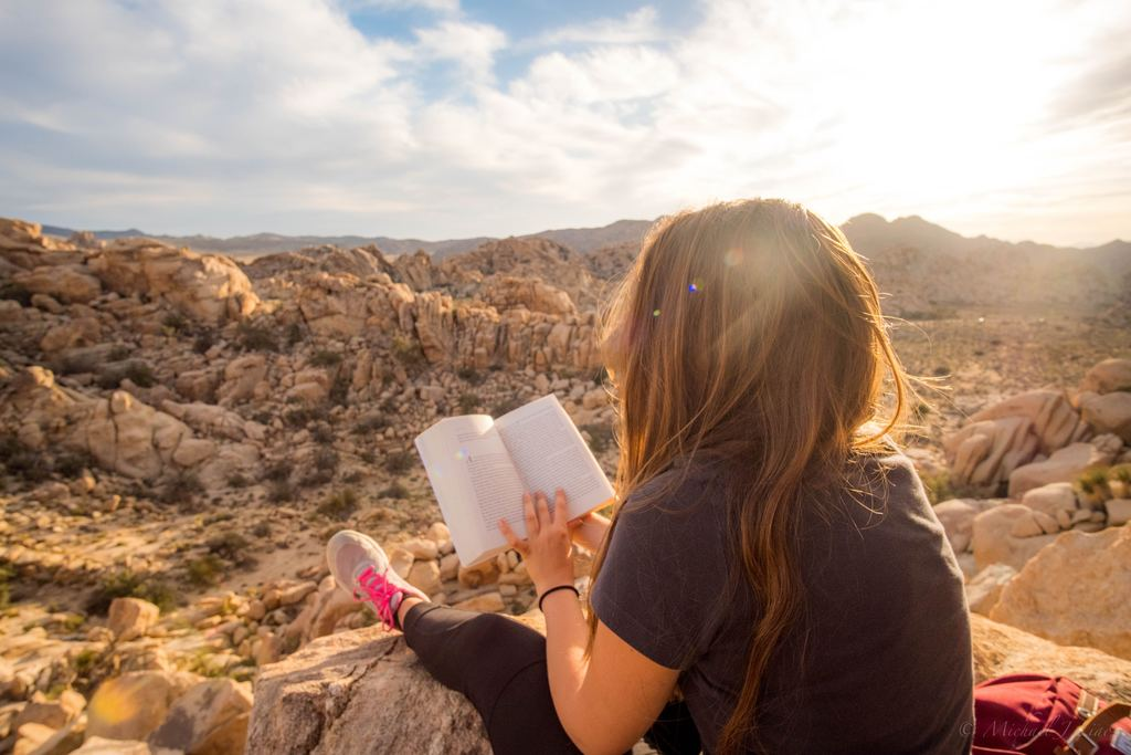 Girl reading on top of cliff