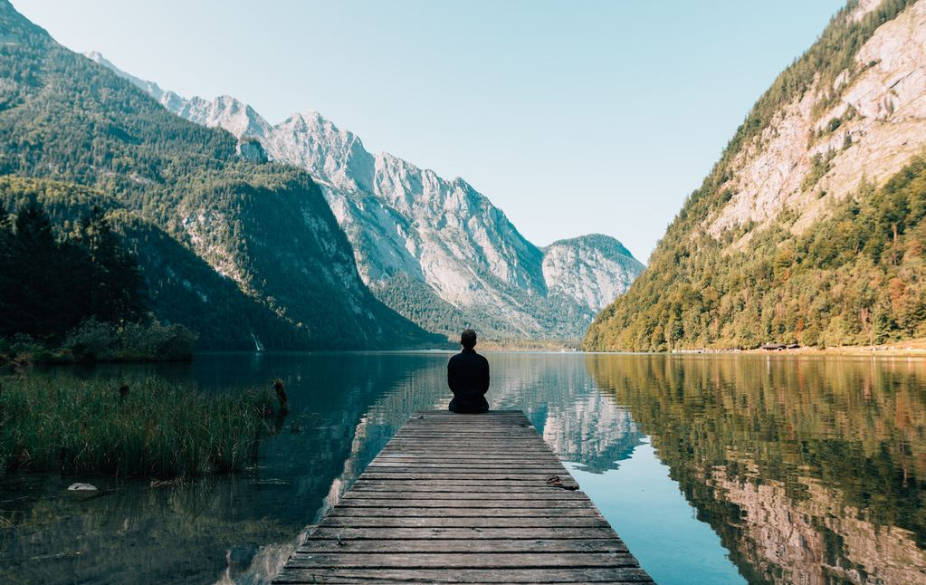 man sitting in front of body of water